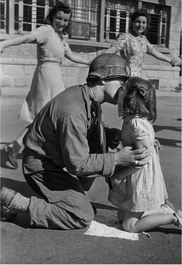 Kiss of Liberation: Sergeant Gene Costanzo kneels to kiss a little girl during spontaneous celebrations in the main square of the town of St. Briac, France, August 14, 1944 © TONY VACCARO - COURTESY MONROE GALLERY OF PHOTOGRAPHY