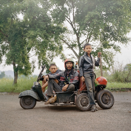 Iponk (middle), a scooterist from South Sumatra along with his son (right) and a travel companion (left). He traveled for hundreds of kilometers, mostly at night to avoid police, to attend a Vespa event in Lampung. © Muhammad Fadli