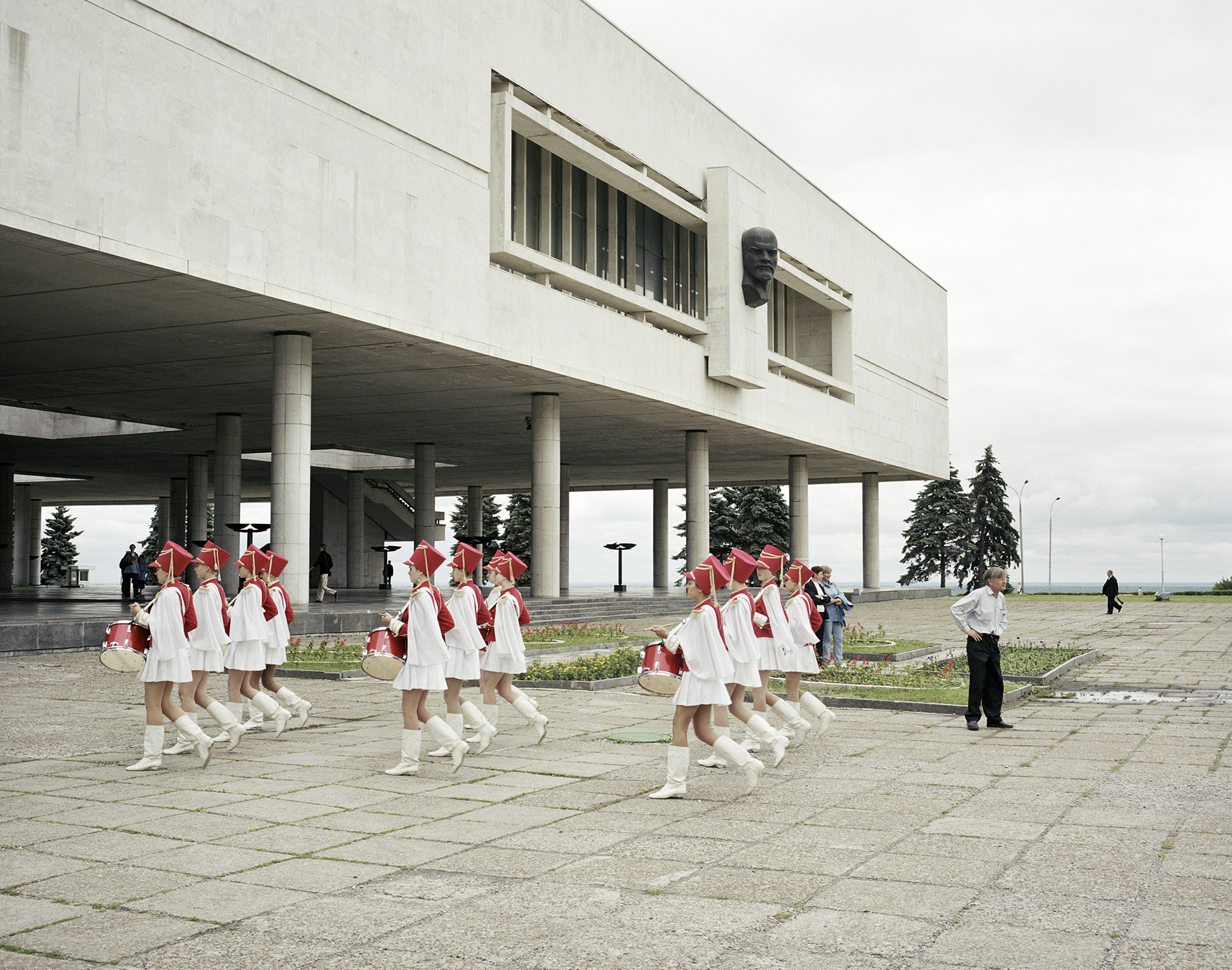 A marching school band pass under Lenin, Ulyanovsk. Volga, June 2005 © Simon Roberts – Courtesy Flowers Gallery