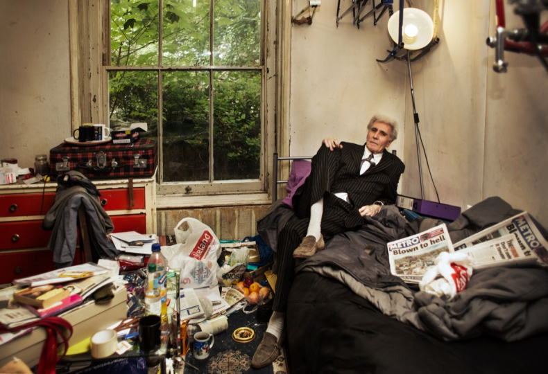 LONDON, UNITED KINGDOM - MAY 22, 2013: Wearing his usual dress-code, George smokes a cigarette in his bedroom May 22, 2013 in London, United Kingdom. Apart from bathroom and toilet, this is the only accessible room in his four-bedroom house. © Corinna Kern