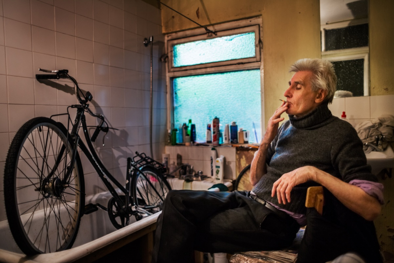 LONDON, UNITED KINGDOM - JUNE 28, 2013: George takes a cigarette break from repairing one of his bikes June 28, 2013 in London, United Kingdom. Due to the limited space in his cramped house, George's bathtub is the most convenient location for repairing bikes. © Corinna Kern