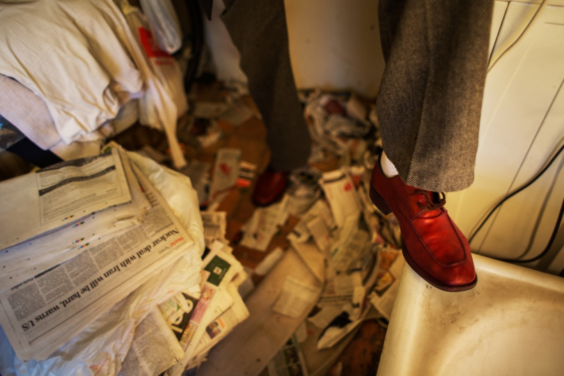 LONDON, UNITED KINGDOM - NOVEMBER 22, 2013: Wearing his freshly polished shoes, George stands in his bathroom filled with piles of newspapers November 22, 2013 in London, United Kingdom. Before throwing away any newspapers or magazines, George makes sure that he reads them to then tear them into pieces that wait on the floor to be removed, often until days or weeks later. © Corinna Kern