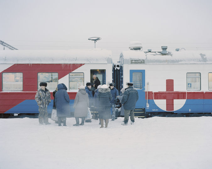 On board the medical train 'Saint Lukas' that travels to remote and underserved towns in Siberia. Patients wait at the entrance to the registration carriage at the beginning of the train. In November 2016 outside temperatures reached until -38° Celsius. Kuragino, Krasnoyarsk Krai, Russia, 12.11.2016. © Emile Ducke