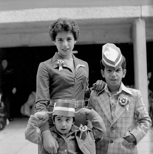 Sheniz Bayraktar (née Mehmet) with her brothers at a celebration of The Queen's Silver Jubilee in South Thamesmead. 1977 Photography © George Plemper