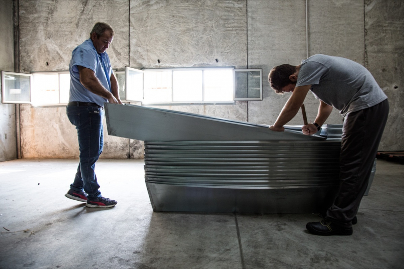 Two mortuary operators assembling the zinc parts of the coffins, in the area of the hangar adjacent to the autopsy tents of the Nato base of Melilli, Sicily © Max Hirzel