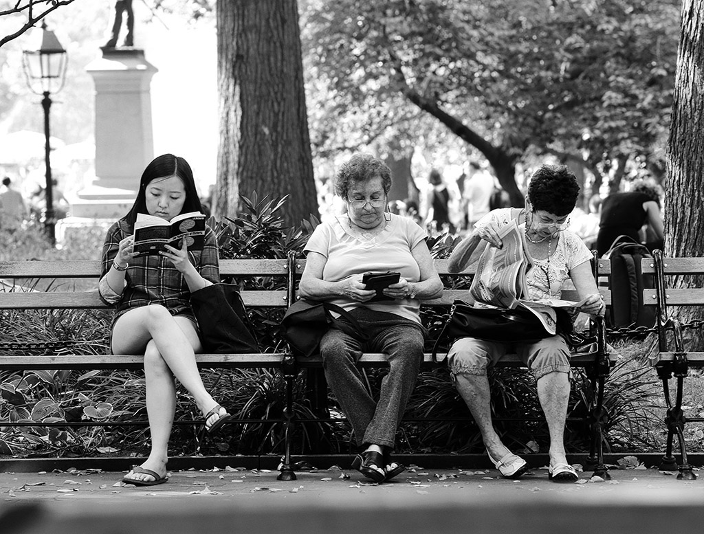 Reading Series--three women reading on a park bench in Washington square Park, October 4, 2013.  © Lawrence Schwartzwald