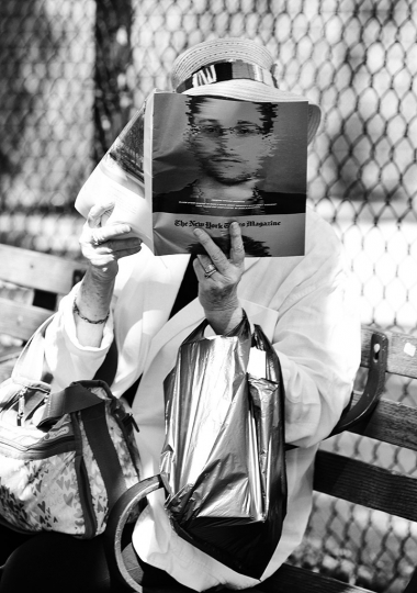 Reading Series--Woman reading a copy of The New York Times Magazine section with Edward Snowden on the cover on a bench on Sixth Avenue off W. Houston Street in Greenwich Village, September 4, 2016 © Lawrence Schwartzwald