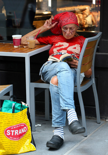 Reading Series—Woman in red bandana reading a book at a sidewalk cafe table on Astor Place, NYC August 16, 2018 © Lawrence Schwartzwald