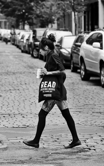 Reading Series--Woman with book bag that reads: READING FUCKING BOOKS ALL DAMN DAY crosses Prince & Wooster in Soho, NYC. July 18, 2015 © Lawrence Schwartzwald