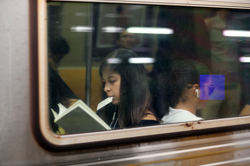 Reading Series—Women Reading— A young woman reads a books with a Metro Card in her mouth on the downtown W train leaving the City Hall Station in Manhattan. © Lawrence Schwartzwald