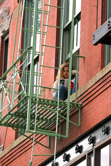 Reading Series--woman reading a book on a fire escape on Houston & Sullivan Streets, NYC May 17, 2018. © Lawrence Schwartzwald