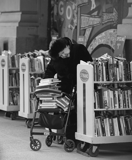 Reading Series--Woman with a walker stacked with books reading in the stacks outside Strand Books at 12th st. and Broadway. March 9, 2014 © Lawrence Schwartzwald