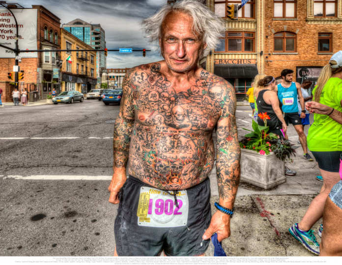 "2. The Gray Haired Man Was Preparing to Run in the Buffalo Pride 2016 5K Race. He Seemed Friendly as I Raised My Camera to Make His Picture, and Asked Me About the Megapixel Size of My Camera's Sensor. I Asked How Long It Took to Apply the Dozens of Tattoos Covering the Front and Back of His Torso, and Complimented Him on the Design and Execution. He Said: ""It Took a Bit Over One Year; He Designed the Pattern Himself; the Work Had Just Been Finished; and Was Something He Wanted Done Before He Got Any Older."" Closely Read, There Were Various Latin Phrases—Some Misspelled: ""I Run Therefore I Am;"" ""Seize the Day;"" and Most Telling, Given the Predominance of Skulls, ""Love Life Because Death Follows."" However, Scattered Among the Skulls Were Tattoos of Hot Peppers, Various Spiders, Eyeballs Trailing Nerve Endings, Cryptic Numbers, Halloween Jack-o'-Lanterns, Butterflies, a Bottle of Tabasco Sauce, Illustrations by Jack Tenniel for Lewis Carroll's ""Alice's Adventures in Wonderland,"" a Mutant Ninja Turtle, and a Portrait of Jim Morrison. Overall, the Look Was Bewildering, and the Message Mixed. But Unlike 98% of the Mostly Retarded Tattoos I've Seen, It Was Not Pure Shit. © Les Krims"