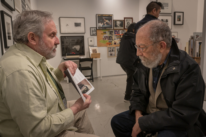 Stephen Cohen shows off something in the catalog to Berkeley photographer Victor Landweber © Andy Romanoff