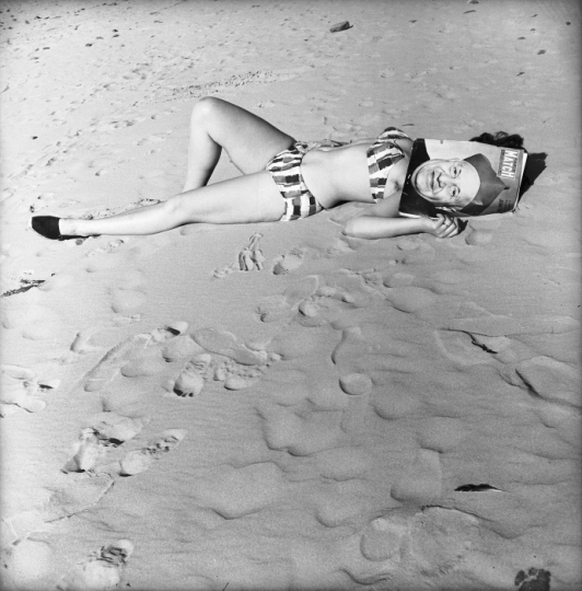 Pin up.Woman lying on the sand with a magazine on the head. © René Maltête – Courtesy Gamma-Rapho