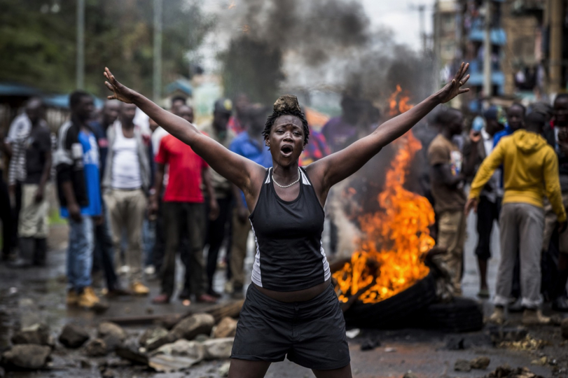 Luis Tato, Spain, Kenya's Post-Election Turmoil, Top news, series, 1st place - An opposition supporter carries a stone on her head under the heavy rain in front a burning barrricade in Mathare, Nairobi on October 26, 2017, as a group of demonstrators attempted to prevent voters from accessing a polling station in presidential elections. Kenyan politics is characterised by inter-ethnic tensions and Kenyan elections were marred by deadly riots, violent protests, killings, and beatings in key opposition strongholds along the country. Human Rights Watch and Amnesty International found that just during the post-electoral process, police and inter-ethnics conflicts killed at least 100 people, and injured hundreds more in several parts of the country.