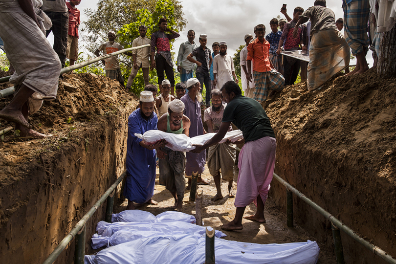 The funeral and burial in a mass grave of Rohingya who drowned when their boat broke up in bad weather trying to land their boat on the Cox's Bazar coast the night before. - No Place On Earth © Patrick Brown