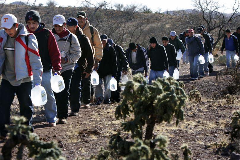 "FEBRUARY 28, 2007. SASABE, SONORA, MEXICO. ""Walking to America"" Lugging jugs of water, migrants from Central America and Mexico march single file on a 3-day hike through the south Arizona desert. I documented the organized smuggling of illegal immigrants from a staging point in Altar, Mexico to Arivaca, Arizona. Mexican drug cartel smugglers charge about $3000 from each person. Mexican government migrant protection officers at a checkpoint on the road to the border said they registered 500 migrants who on this day. (Photograph by Don Bartletti)"