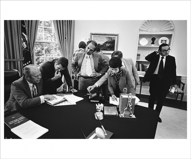 May 27, 1975 Preparing for a televised address on the energy crisis, President Ford consults with his staff: Among them chief of staff Donald Rumsfeld, press secretary Ron Nessen, deputy chief of staff Dick Cheney, (putting a cigarette out in the ashtray on the president's desk), and economic advisor Alan Greenspan. (Photo by David Hume Kennerly/Gerald R. Ford Presidential Library)
