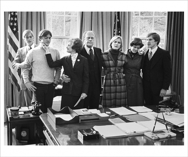 November 3, 1976 After President Ford conceded the election in a phone call to Jimmy Carter, the Ford family gathered in the Oval Office and Mrs. Ford as always tried to remain upbeat. A few minutes later she delivered the concession remarks in the White House press room because the president had lost his voice during the final days of the campaign. From left are sons Steve and Jack, daughter Susan, daughter-in-law Gayle, and son Mike. (Photo by David Hume Kennerly/Gerald R. Ford Presidential Library)