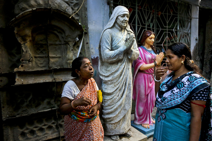 © Kumortuli - Local resident women sips tea while chat beside the moulded statues of Saint Teresa and other decorative items on a street of Kumortuli, the potter's place, in Kolkata, India, Friday, Aug. 31, 2018.