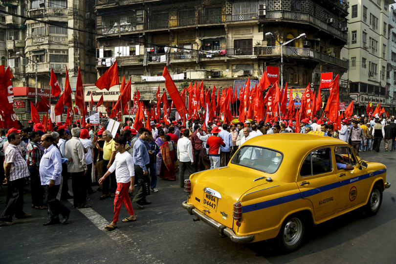 A yellow taxi rolls past as cadres and supporters of seventeen left party alliance led by Communist Party of India-Marxist (CPI-M) prepare for non-communal harmony and solidarity in country, in Kolkata, India, Thursday, Dec. 6, 2018. Hard-line Hindus are demanding a Hindu temple be built on a site in northern India where they in 1992 had attacked and demolished a 16th century mosque on this day, sparking deadly Hindu-Muslim violence.
