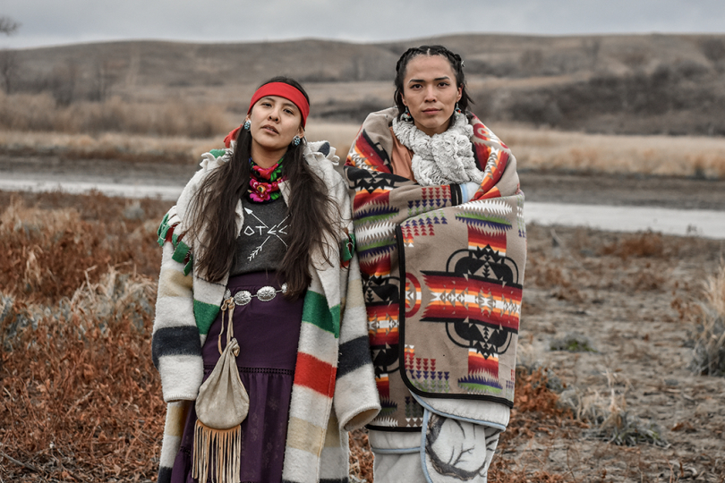 Two Dine woman hold strong in sovereignty, only speaking their ancestral language at Turtle Island, Thanksgiving, 2016 © Ryan Vizzions – Courtesy Monroe Gallery of Photography