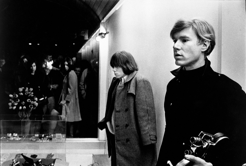 Brian Jones and Andy Warhol at Paraphernalia launch, New York City, 1966 (Brian Jones, founding member of the Rolling Stones, and Andy Warhol at launch party for Paraphernlia boutique, New York City, 1966.) - © Nat Finkelstein Estate – Courtesy Proud Galleries