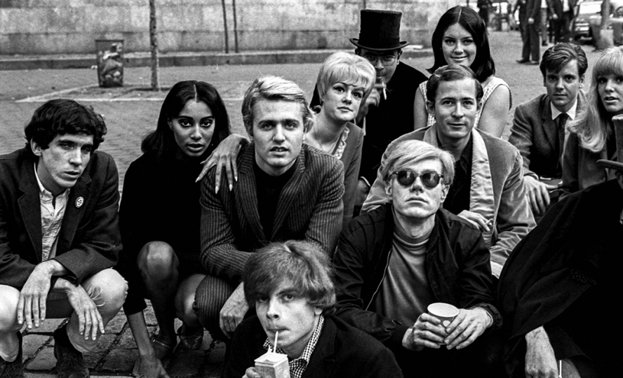 Andy Warhol with Group at Bus Stop, New York City, 1966 (Warhol and friends including Gerard Malanga, Donyale Luna, Ingrid Superstar, Danny Williams, David Dalton, Sarah Dalton, and others) - © Nat Finkelstein Estate – Courtesy Proud Galleries