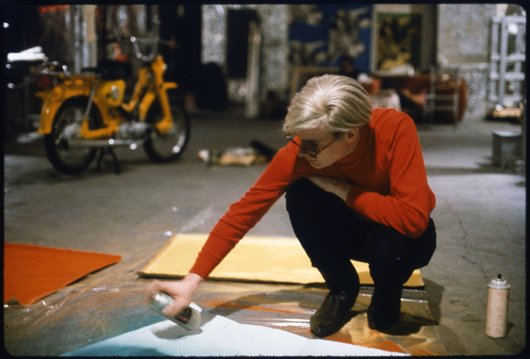 Andy Warhol with Spray Paint and Moped, The Factory, c. 1965 (Color image of Andy Warhol at work at the Factory, New York City, circa 1965) - © Nat Finkelstein Estate – Courtesy Proud Galleries