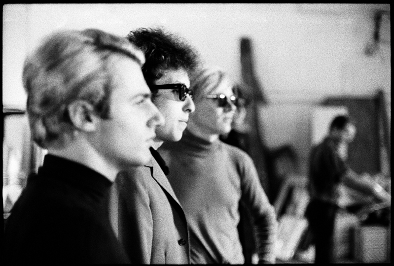 Gerard Malanga, Bob Dylan, Andy Warhol (in profile), The Factory, 1966 (Photograph from Bob Dylan's visit to Andy Warhol's Factory for filming of screen test. Gerard Malanga, author and Factory assistant, featured in foreground.) - © Nat Finkelstein Estate – Courtesy Proud Galleries