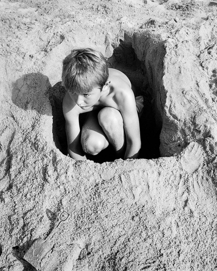 BOY IN SAND HOLE, 1988 © Mimi Plumb – Courtesy Robert Koch Gallery