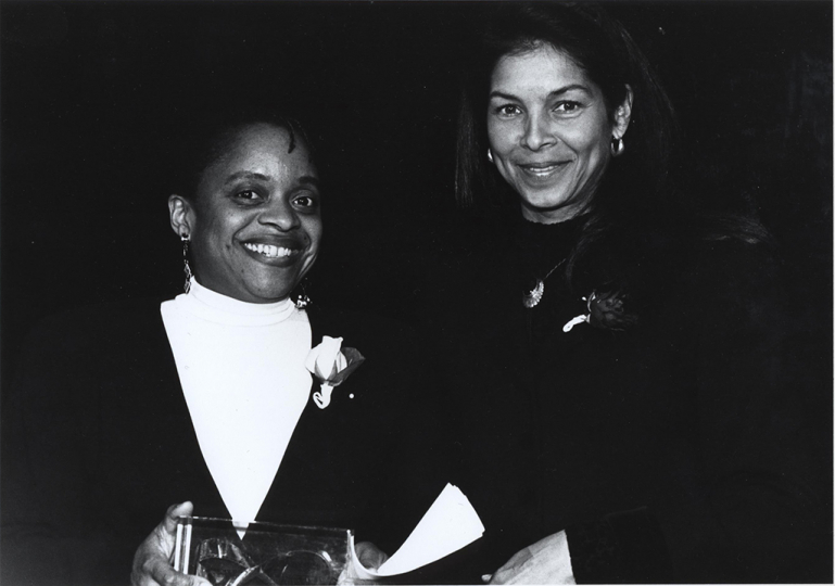 Deborah Willis receiving the Writing Award from Jeanne Moutoussamy-Ashe at the 1995 Infinity Awards. Courtesy International Center of Photography. Photo by David J. Spear.