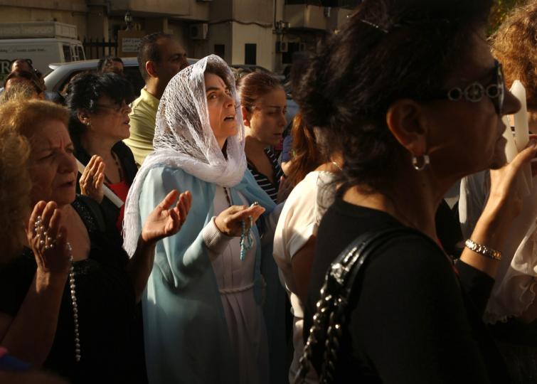 A Lebanese Maronite Christian woman dressed as Virgin Mary prays during a procession marking the month of Virgin Mary in the town of Jdeideh, north-east of Beirut, on May 21, 2016. © AFP / Patrick Baz