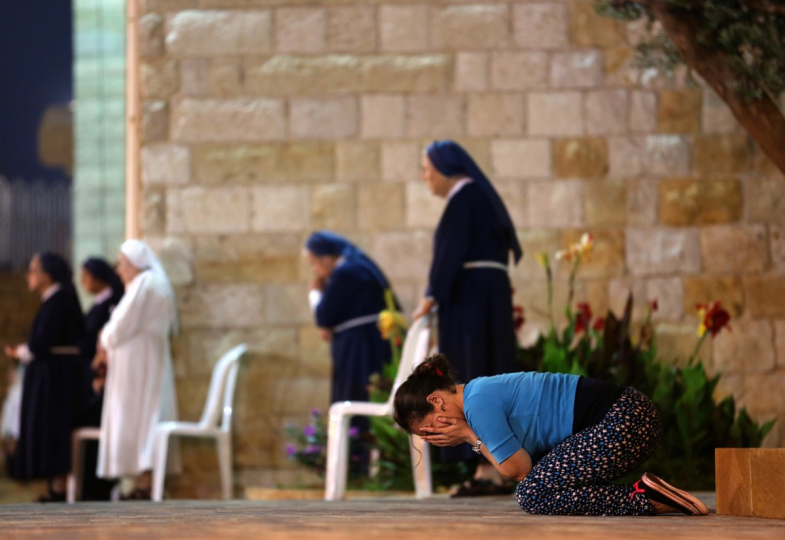 A woman prays in front of Christian Maronite nuns during a mass commemorating Father Jacques at the Monastery of the Cross in the Lebanese town of Jal el-Dib, north of Beirut, on June 22, 2016. Father Jacques Haddad, a Lebanese monk, was an intinerent preacher in the Levant. He died on June 26, 1954 in Lebanon and was beatified on June 22, 2008. © AFP / Patrick Baz