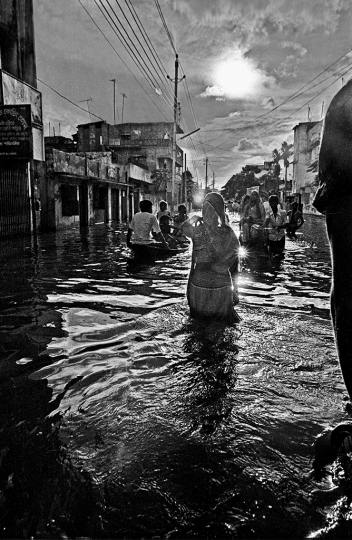 Woman wading in flood, Kamalapur, Dhaka, Bangladesh. 1988. - Photo by Shahidul Alam 1988