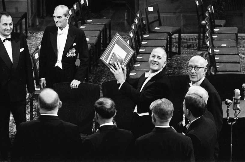 Nobel Prize Ceremony, Stockholm, November 1958. Dr. George Beadle from Caltech in Pasadena, California, winner of the Nobel Prize in 1958 for developing the one gene, one enzyme theory, raises his Nobel Prize for Baldwin's camera. © Fred Baldwin