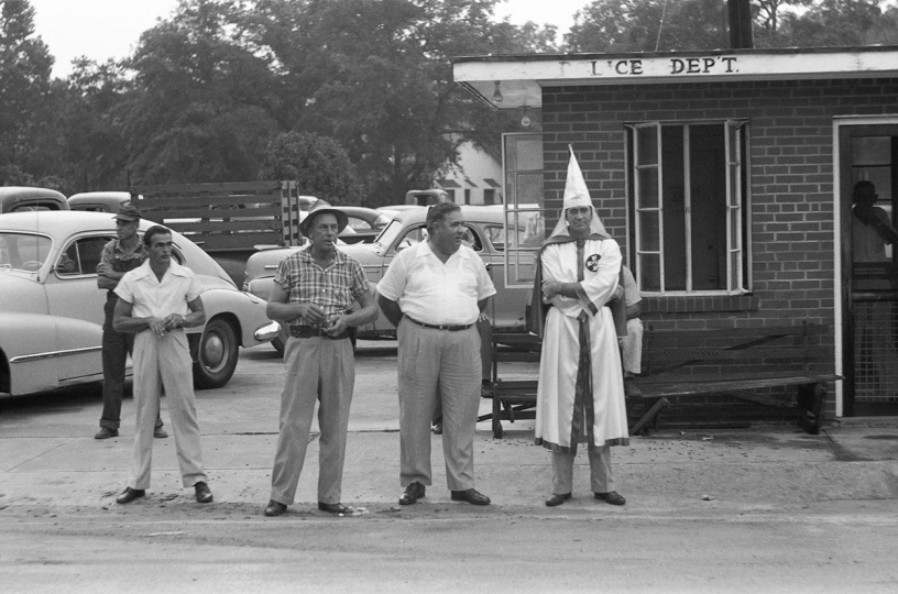 Ku Klux Klan, Reidsville, Georgia, 1966 – A Klan member, the Chief of Police and the Sheriff wait for the decorated KKK cars on their way to a ceremony to pass by. © Fred Baldwin