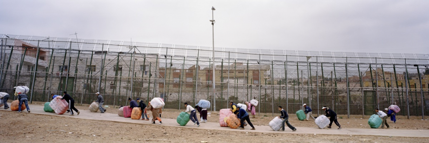Marrocans pushing package of clothes towards a borderentrance to Marroco from the Spanish enclave of Mellila. The fence was erected over the last decade to prevent immigration from Africa to the European Union. © Kai Wiedenhöfer